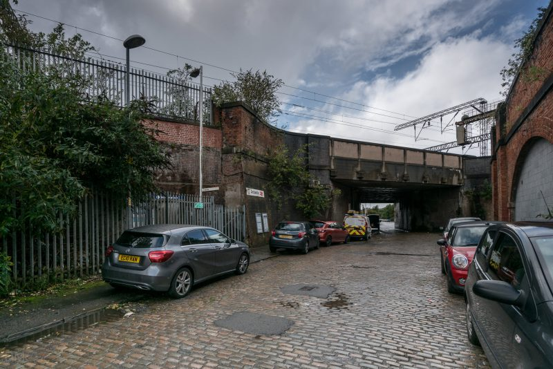 Cars parked on Blind Lane, near the entrance to Ardwick Train Station