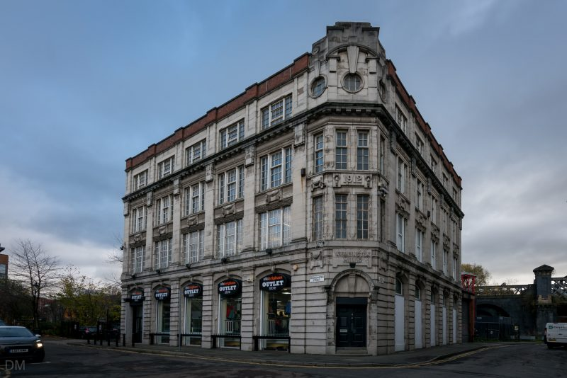 Photo of the Wellington Mills building, at the corner of Duke Street and Bridgewater Street in Castlefield, Manchester. At the time the photo was taken (November 2017) the ground floor was occupied by the Ellis Brigham Outlet Store.
