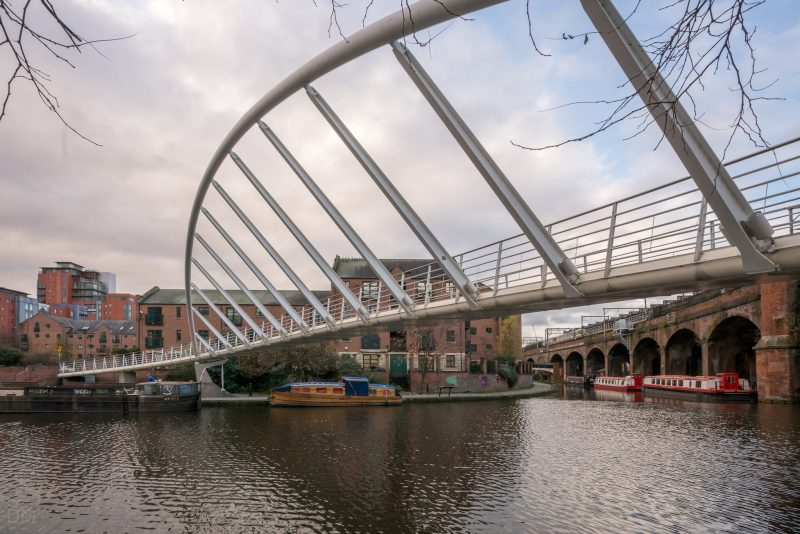 Photograph of Merchants' Bridge in Castlefield, Manchester. The iconic pedestrian bridge passes over the Castlefield Basin, linking Slate Wharf to Catalan Square.