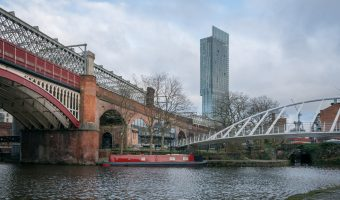 Photo of the Castlefield Basin in Manchester. Merchants' Bridge can be seen and connects Slate Wharf to Catalan Square. The Beetham Tower can be seen in the background.