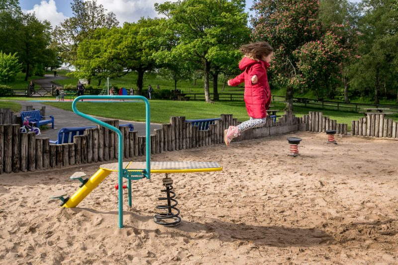 Photograph of a girl jumping off a diving board into the sandpit at Moss Bank Park in Bolton.