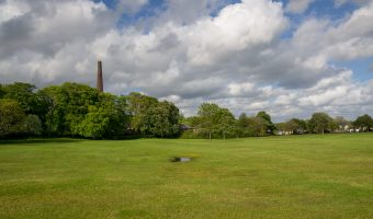 Photo of a playing field at Moss Bank Park in Bolton. 'Barrow Bridge Chimney' can be seen in the distance and is all that remains of Halliwell Bleach Works.