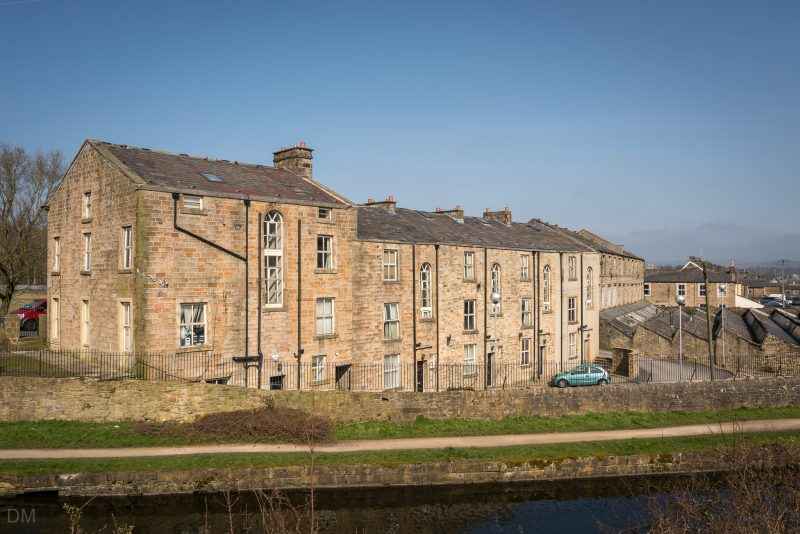Photograph of houses on Westgate in Burnley. Viewed from Trafalgar Street. The Leeds and Liverpool Canal is in the foreground.