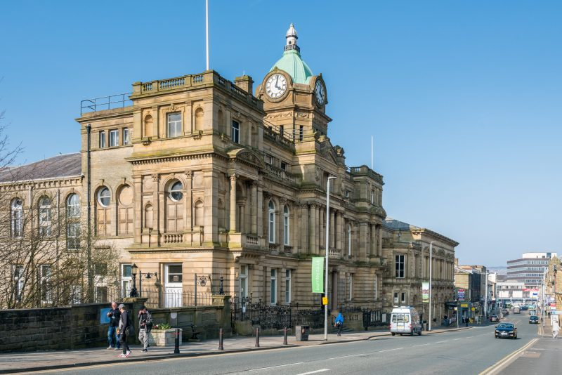 Photograph of Burnley Town Hall on Manchester Road in Burnley. Burnley Mechanics, a live music venue, can also be seen.
