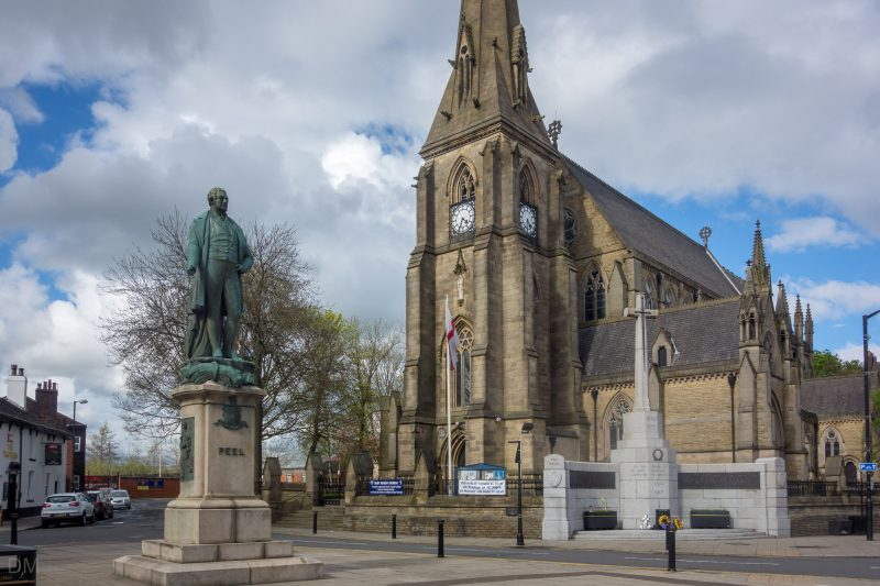 Photo of Bury Parish Church (aka Church of St Mary the Virgin, Bury). The Peel Memorial, a statue by Edward Hodges Bally, can also be seen.