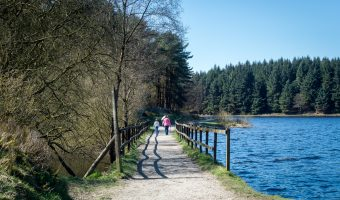 Walkers crossing the footbridge on the southern side of Turton and Entwistle Reservoir in Edgworth.