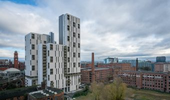 Photograph of apartment buildings on Cambridge Street in Manchester. From left to right; One Cambridge Street, Chorlton Mills, and Macintosh Mills.