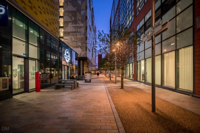 Photograph of Jack Rosenthal Street at First Street in Manchester city centre. Entrance to Q-Park First Street (car park) and the Kettlebell Kitchen restaurant on the left. Number One First Street (office building) on the right.