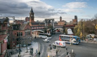 Photo of the junction of Deansgate and Whitworth Street West in Manchester. From left to right; Deansgate Train Station, Atlas (bar), The Knott (bar), and the Rochdale Canal.