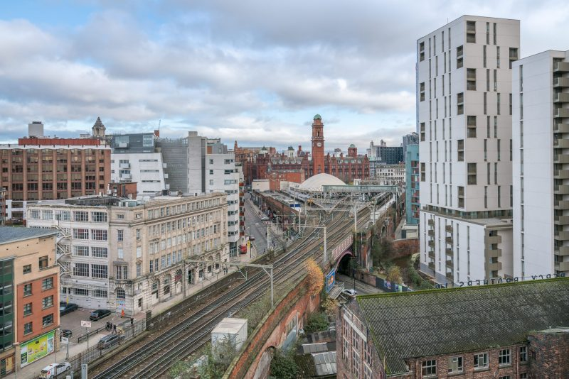 Photograph of Manchester Oxford Road Train Station. Whitworth Street West can also be seen. The building on the right in One Cambridge Street (apartments).