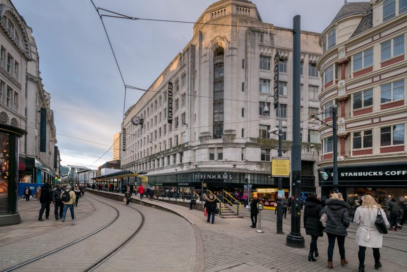 Photo of the Market Street Tram Stop (Metrolink) on Market Street in Manchester. The Debenhams department store can also be seen.