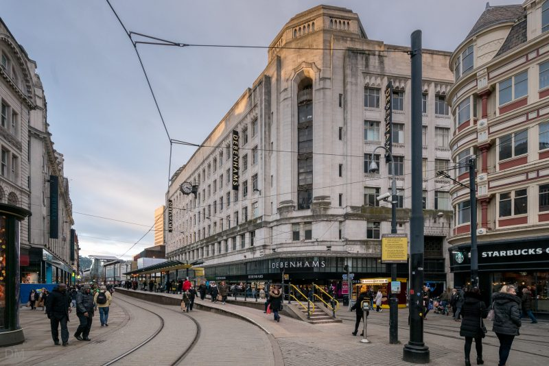 Photo of Market Street in Manchester city centre. The photograph shows the Market Street Tram Stop and the Debenhams department store.