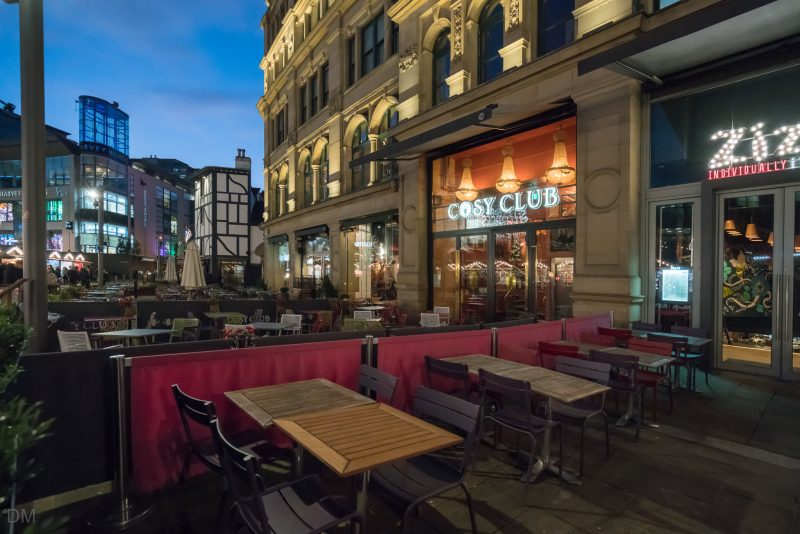 Photo of the exterior of the Corn Exchange restaurant complex in Manchester city centre. Harvey Nichols can be seen in the distance.