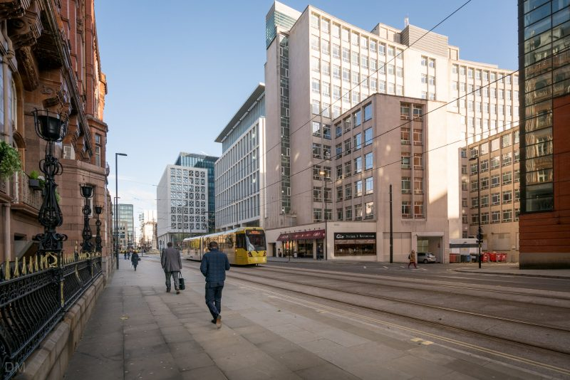 Photo of Metrolink trams on Lower Mosley Street in Manchester city centre. The trams have just left St Peter's Square Tram Stop.