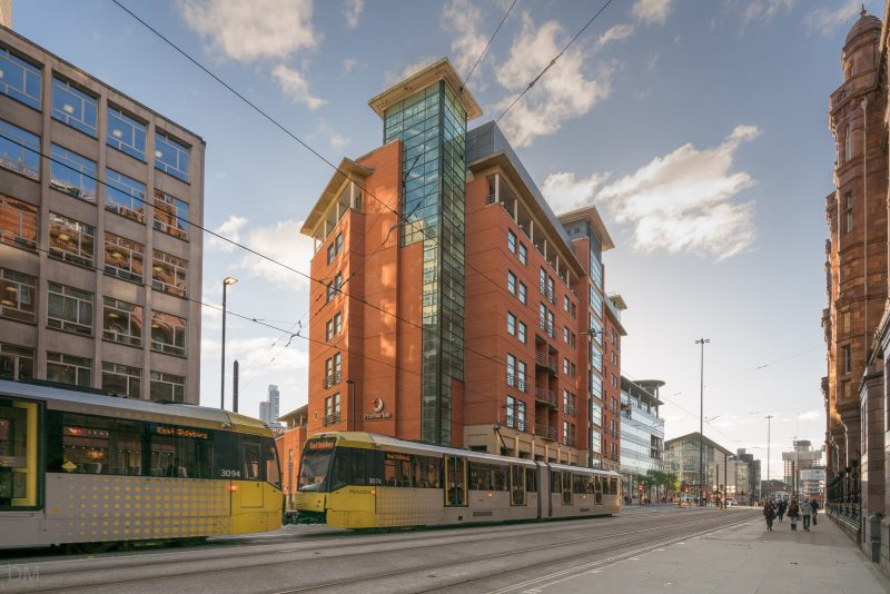 Photo of a Metrolink Tram passing the Premier Inn Manchester Central on Lower Mosley Street. The Bridgewater Hall can be seen in the distance.