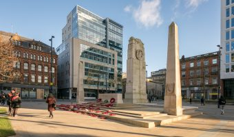 Photo of the Manchester Cenotaph on St Peter's Square in Manchester city centre. 80 Mosley Street, an office building, is in the background.