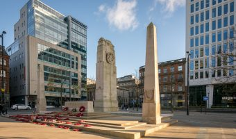 Photograph of the Manchester Cenotaph, St Peter's Square, Manchester. 80 Mosley Street, an office building is on the left of the photo. Two St Peter's Square, also offices, is on the right.