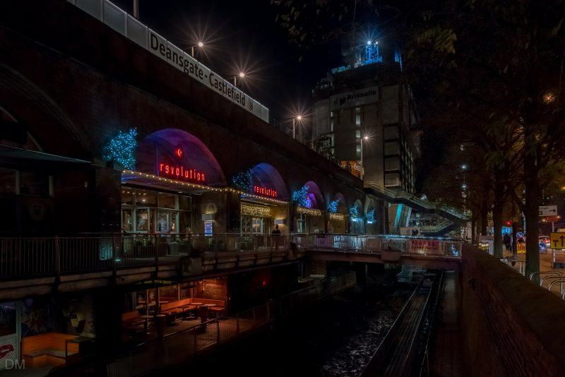 Photograph of Deansgate Locks at night. The Deansgate-Castlefield Tram Stop is above the station.