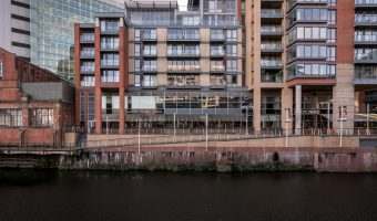 Photograph of the Leftbank Apartments at Spinningfields in Manchester city centre. The ground floor is occupied by businesses such as Gourmet Burger Kitchen (burger restaurant) and The Dockyard (pub).
