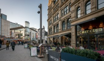Photo of Exchange Square in Manchester city centre. Selfridges, Harvey Nichols, and the Cosy Club restaurant at the Corn Exchange can be seen.