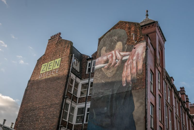 Street art on the wall of the Swan Buildings on Cable Street, Ancoats, Manchester. The mural is Human Dignity is Inviolable by German artist Case (Andreas von Chrzanowski).