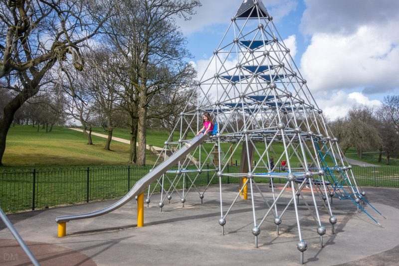 Photo of the pyramid climbing frame and slide at Queens Park in Bolton.