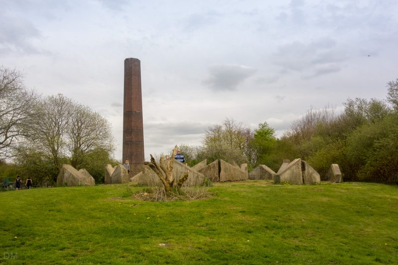 Photograph of the Stone Cycle sculpture at Burrs Mill Country Park, Bury. The chimney of Burrs Mill can also be seen.