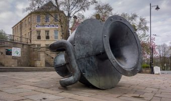 Photo of the Tilted Vase sculpture on Market Place in Ramsbottom. Ramsbottom Civic Hall can also be seen.