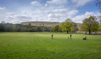 Photo of a playing field at Nuttall Park in Ramsbottom. Peel Tower and Holcombe Hill can be seen in the distance.