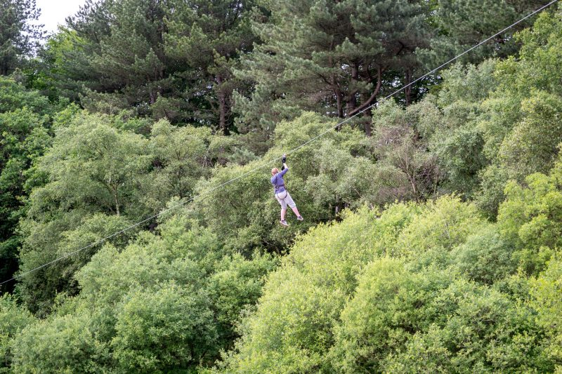 Woman on the zip line over Lower Rivington Reservoir at Go Ape, Rivington.