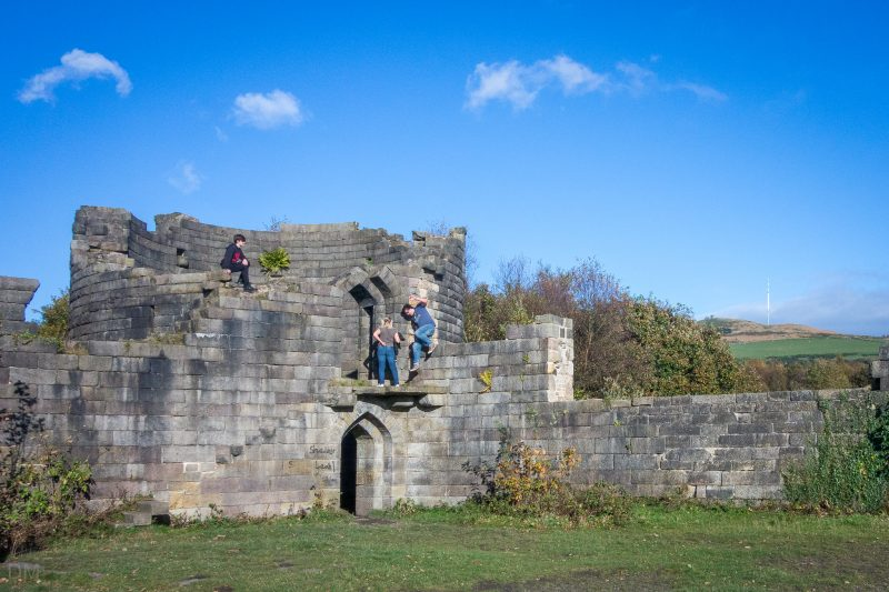 People climbing on the North West Tower at Liverpool Castle in Rivington, Lancashire. The Winter Hill Transmitting Station can be seen in the background.