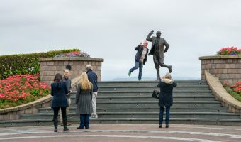 Tourists posing for photographs next to the Eric Morecambe statue on Morecambe Promenade.
