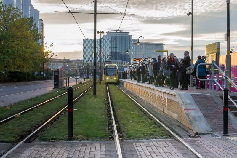 Photo of passengers waiting for a Metrolink tram at Harbour City Tram Stop in Salford Quays. The Orange Tower, an office building at MediaCityUK, can be seen in the distance.