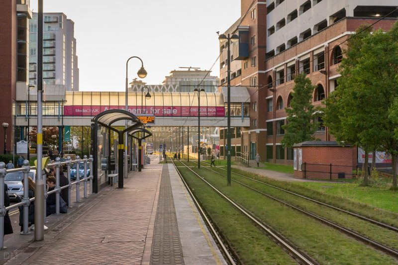 Photograph of Harbour City Tram Stop. The Metrolink station opened in 1999 and is located at Salford Quays. The Victoria, an office building, can be seen on the right.