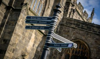 Photograph of a signpost giving directions to tourist attractions in Lancaster. Located near Lancaster Priory.