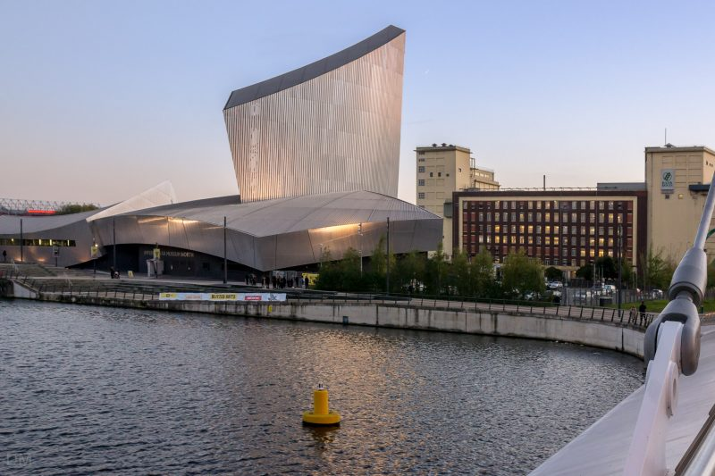 Photograph of the Imperial War Museum North at Salford Quays. The Rank Hovis Flour Mill on Trafford Wharf Road is to the right of the image. The Old Trafford football stadium can just be seen on the left.