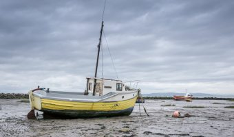 Photograph of a fishing boat for sale at Morecambe Bay. Taken from Morecambe Promenade.