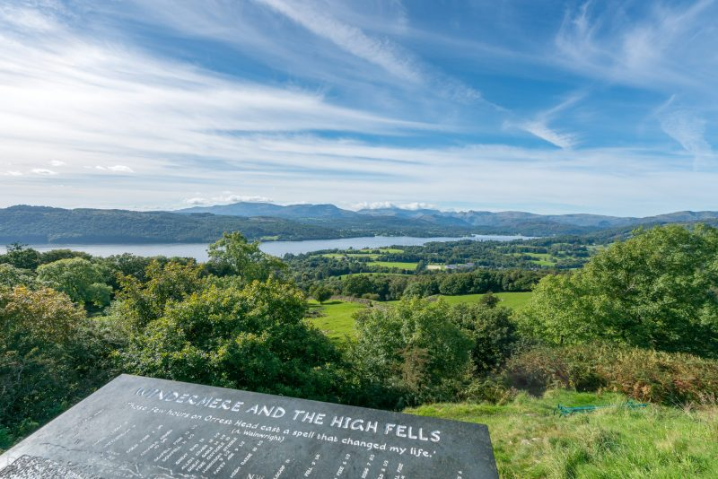 View of Windermere from Orrest Head. A slate toposcope is in the foreground of the picture. It was installed by Windermere Town Council and the Wainwright Society. It shows the names of the visible fells and other features.