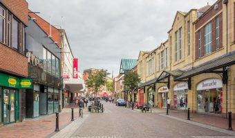 Photograph of Friargate, a busy shopping street in Preston city centre. The St George's Shopping Centre is on the right.