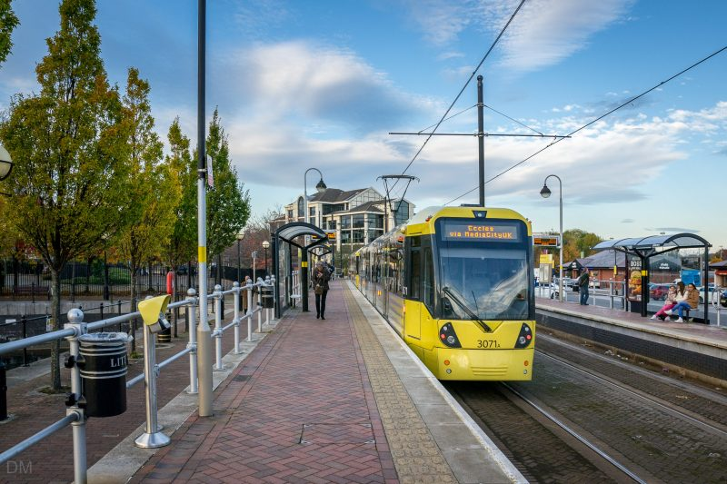 Photo of Metrolink tram at Salford Quays Tram Stop. Ontario House, an office building, can be seen in the distance.