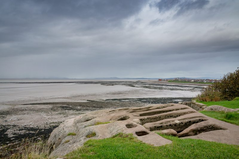 Photograph of the stone graves near St Patrick's Chapel, Heysham, Lancashire. Morecambe and Morecambe Bay can be seen.