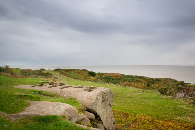 Photo of the stone graves at St Patrick's Chapel in Heysham. Morecambe Bay can be seen.