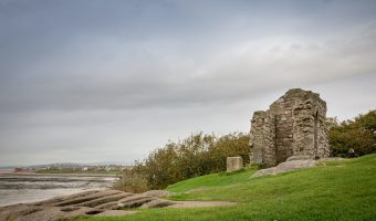 Photo of St Patrick's Chapel and the stone graves in Heysham. Morecambe Bay can be seen.