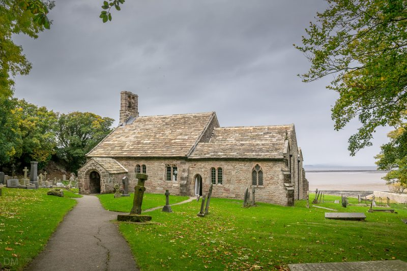 Photograph of exterior of St Peter's Church, Heysham. Morecambe Bay can be seen in the distance.