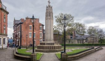 Photograph of the Wigan War Memorial in Wigan town centre. The memorial was unveiled in October 1925 and was designed by Sir Giles Gilbert Scott. It is located by Wigan Parish Church.