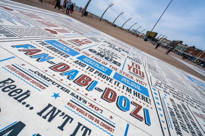 Photo of the Comedy Carpet in Blackpool. The slab shown includes phrases from Vic Reeves Big Night Out ('What's on the end of the stick Vic?'), Little Britain ('Computer says 'No'), and the Krankies ('Fan-Dabi-Dozi').