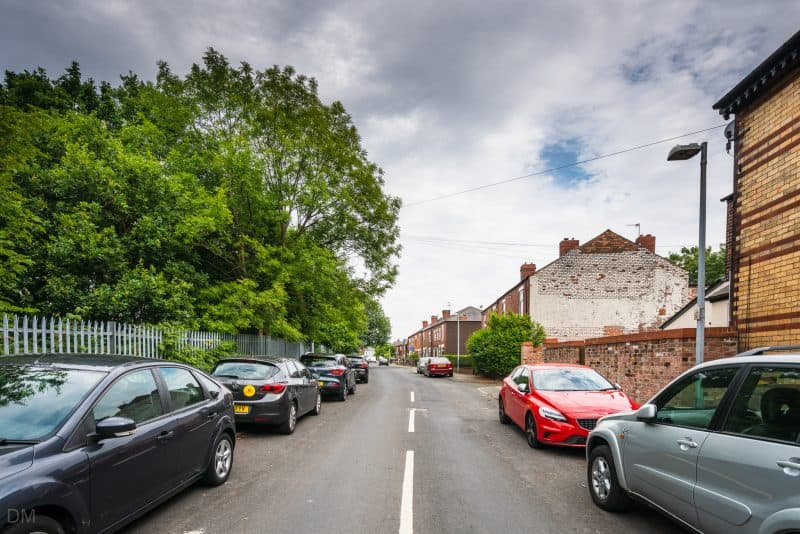Cars parked on Reginald Street, next to Moorside Train Station in Swinton, Greater Manchester.