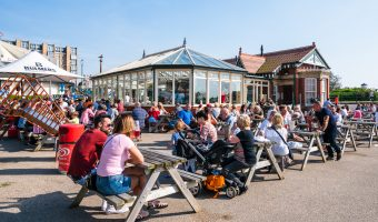 People sat at tables outside Marine Lake Cafe at Marine Lake/King's Gardens in Southport, Merseyside.