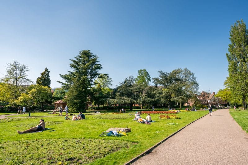 People sunbathing on the lawn at Grosvenor Park in Chester.